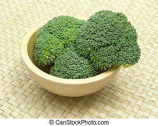 Wooden bowl with broccoli on rattan underlay