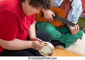 Mentally disabled woman playing a tamborin - a mentally...