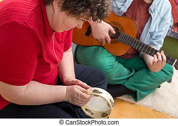 Mentally disabled woman playing a tamborin