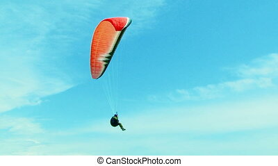 One Paraglider Soaring In the Sky - Two frames: one...
