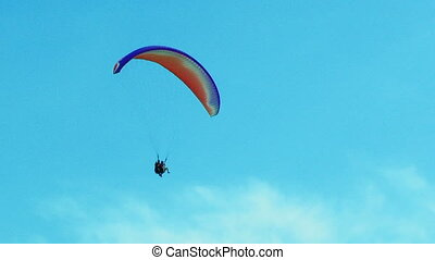 Several Paragliders Soaring In Blue Sky - Tracking shot of...