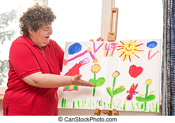 mentally disabled woman showing her painting - a mentally...
