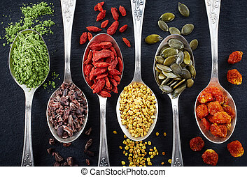 Superfoods - Spoons of various superfoods on black...