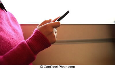 woman use cellphone on train - young woman use her cellphone...