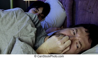 Man crying in bed with sleeping girlfriend