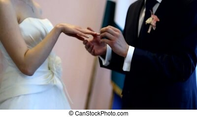 Putting a wedding ring on bride's finger - Groom putting a...