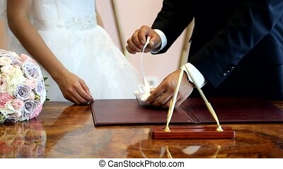 Putting a wedding ring on brides finger - Groom putting a...