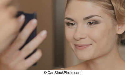 Girl with make-up looks at herself in a mirror - Girl with...