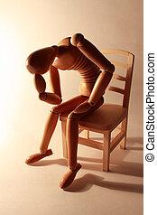 worried wooden dummy sitting