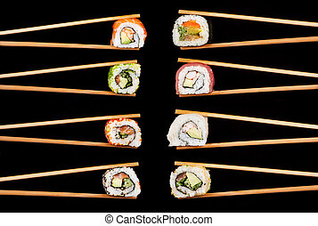 Sushi pieces in chopsticks - Set of sushi pieces in...