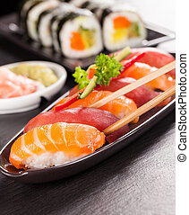 Delicious sushi salmon rolls served on black plate and stone