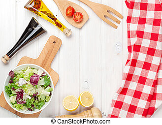 Fresh healthy salad and condiments over white wooden table...