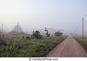 summer end rural gravel road and morning mist