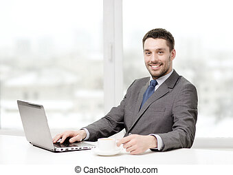 smiling businessman with laptop and coffee - office,...