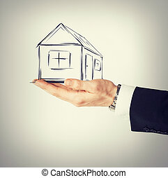 house on virtual screen in man hand - real estate,...