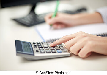 close up of woman with calculator taking notes - finances,...