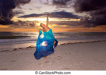 joyous dance on beach - a happy blonde haired woman is...