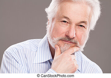 Handsome elderly man with grey beard over background