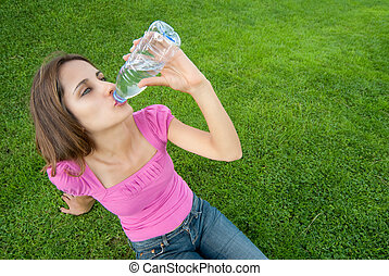 Woman drink water grass - Young woman drink water sit grass