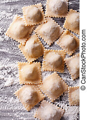 raw ravioli with flour on the table. Vertical top view