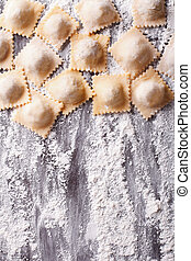 uncooked ravioli with flour on the table. Vertical top view