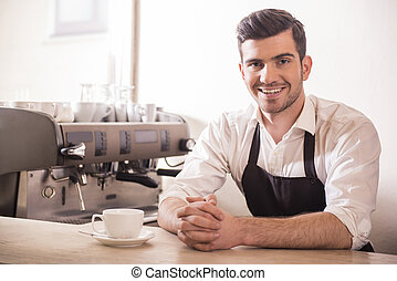 Barista prepares cappuccino in his coffee shop