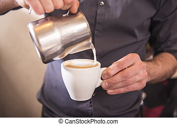 Barista hands is pouring milk making cappuccino.