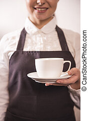 Barista - Pretty young barista is offering cup of coffee in...