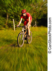 Mountain Biking with copy space. Man in red riding a...