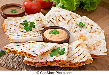 Mexican Quesadilla sliced with vegetables and sauces on the...