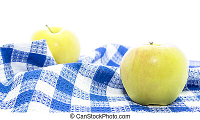 Fresh yellow apple healthy fruit on folded blue tablemat on...