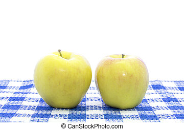 Fresh yellow apple fruit on blue tablemat and white...