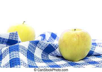 Fresh yellow apple healthy fruit on blue tablemat on white...