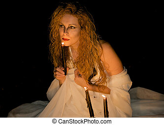 Attractive woman blowing out a candle. - Spooky image of an...