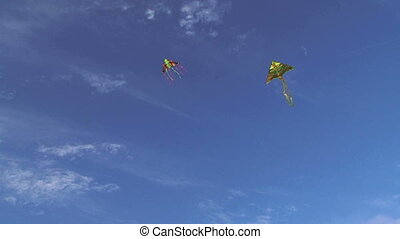 Two Multicolored Kites Flying High In Blue Sky