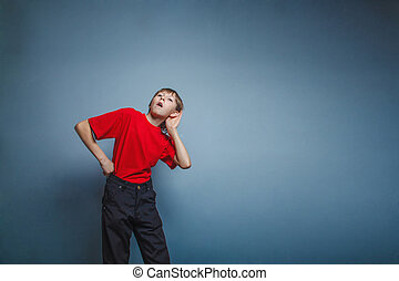 Boy, teenager, twelve years a in red shirt holding his ear...