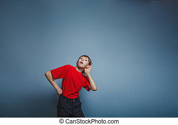 Boy, teenager, twelve years in a red shirt holding his ear...