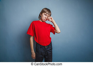 Boy, teenager, twelve years in the red T-shirt, hand wipes...