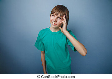 Boy, teenager, twelve years old, green a in t-shirt holding...