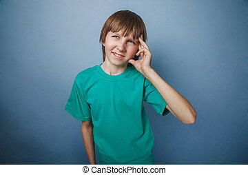 Boy, teenager, twelve years old, a in green t-shirt holding...