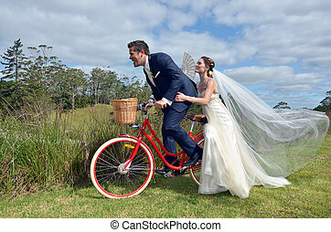 Husband and wife ride on bicycle on their wedding...