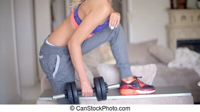 Athletic blond with a sporty toned body lifting weights in...