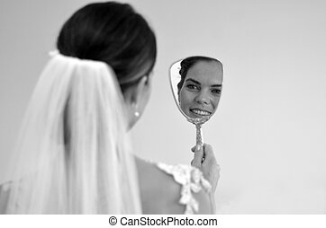 Bride looks at herself in the mirror on her Wedding Day -...