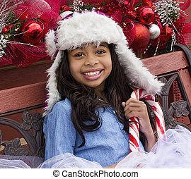 Holiday Girl with Candy Cane - Cute girl sitting on a bench...