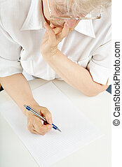 Considering - The elderly woman writes something on a sheet...