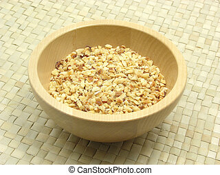 Wooden bowl with roasted chopped hazelnuts on rattan...