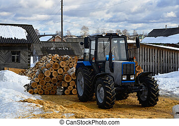 tractor - new tractor and birch logs stacked behind him
