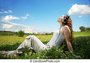 Enjoy music! - The girl with headphones against park and the...