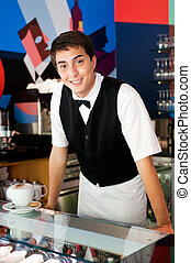 Young Waiter - A young and attractive waiter stands behind...