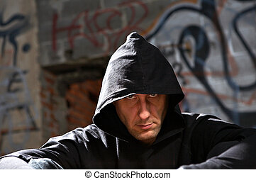 Stranger - Portrait of the man in a hood against an...